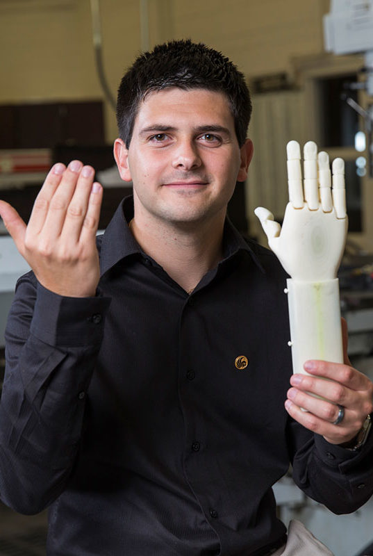 Albert Manero holding up a prosthetic arm in one hand while he raises his other hand to compare